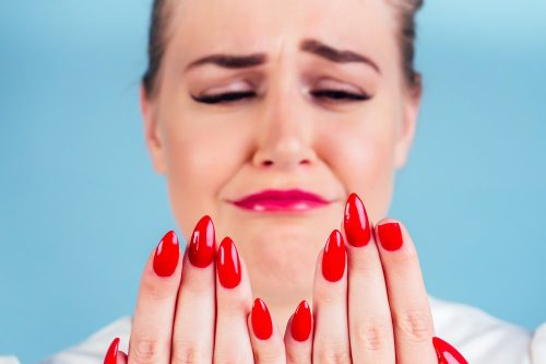 close-up portrait of nervous unhappy young blonde woman looking at a broken fingernail and crying . red long nails manicure broken nail blue background in studio.